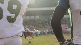 Παιχνίδι αμερικανικού ποδοσφαίρου στην πίσσα, παίκτες υποκατάστατων στην ομοιόμορφη αντιστοιχία προσοχής απόθεμα βίντεο