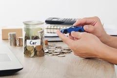 Παιχνίδι αυτοκινήτων εκμετάλλευσης χεριών ατόμων στο σωρό νομισμάτων για το ασφαλιστική δάνειο ή την αποταμίευση για την έννοια α Στοκ Εικόνες
