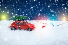 Παιχνίδι αυτοκινήτων που φέρνει ένα χριστουγεννιάτικο δέντρο με τα φω'τα Χριστουγέννων στο β Στοκ εικόνες με δικαίωμα ελεύθερης χρήσης