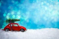 Παιχνίδι αυτοκινήτων που φέρνει ένα χριστουγεννιάτικο δέντρο Στοκ Φωτογραφίες