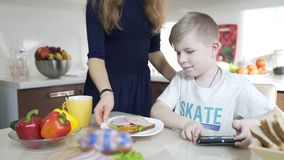 Παιχνίδι γιων με το κινητό τηλέφωνο, Mom που προετοιμάζει το σάντουιτς για το γιο, ευτυχής οικογένεια φιλμ μικρού μήκους