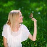 Παιχνίδι γυναικών με μια πεταλούδα Στοκ Εικόνες