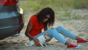 Παιχνίδι γυναικών με τη συνεδρίαση σκυλιών της κοντά στο αυτοκίνητο απόθεμα βίντεο
