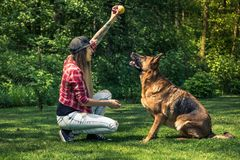 Παιχνίδι γυναικών με το σκυλί της στον κήπο στο καλοκαίρι Στοκ φωτογραφία με δικαίωμα ελεύθερης χρήσης