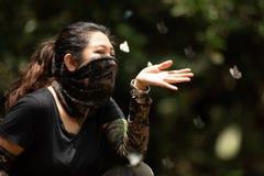 Παιχνίδι γυναικών οδοιπόρων με μια πεταλούδα στοκ φωτογραφία με δικαίωμα ελεύθερης χρήσης