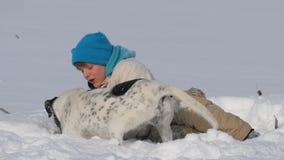 Παιχνίδι διασκέδασης εφήβων αγοριών με ένα σκυλί το χειμώνα στο χιόνι απόθεμα βίντεο