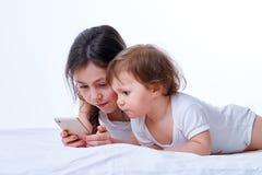 Παιχνίδι δύο αδελφών μαζί στα παιχνίδια στο smartphone στο άσπρο υπόβαθρο στούντιο Στοκ Εικόνες