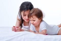 Παιχνίδι δύο αδελφών μαζί στα παιχνίδια στο smartphone στο άσπρο υπόβαθρο στούντιο Στοκ Εικόνα