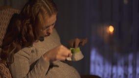 Παιχνίδι εγκύων γυναικών με κάλτσες τις μικρές μωρών που κάθονται στο λίκνισμα της καρέκλας στο σκοτεινό δωμάτιο απόθεμα βίντεο