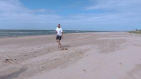 Παιχνίδι ζεύγους με το δίσκο Frisbee στην παραλία απόθεμα βίντεο