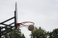 Παιχνίδι καλαθοσφαίρισης οδών Ασπίδα καλαθοσφαίρισης, σφαίρα που περνά από το καλάθι στο υπόβαθρο του ουρανού, δέντρα Έννοια του  Στοκ εικόνα με δικαίωμα ελεύθερης χρήσης