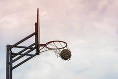 Παιχνίδι καλαθοσφαίρισης οδών Ασπίδα καλαθοσφαίρισης, σφαίρα που περνά από το καλάθι στο υπόβαθρο του ουρανού Έννοια του αθλητισμ Στοκ φωτογραφία με δικαίωμα ελεύθερης χρήσης