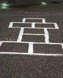 Παιχνίδι κιμωλίας hopscotch στην άσφαλτο στοκ εικόνα