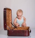 Παιχνίδι κοριτσάκι με τη βαλίτσα στην γκρίζα ανασκόπηση στοκ εικόνα με δικαίωμα ελεύθερης χρήσης