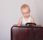 Παιχνίδι κοριτσάκι με τη βαλίτσα στην γκρίζα ανασκόπηση στοκ φωτογραφία