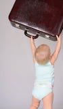 Παιχνίδι κοριτσάκι με τη βαλίτσα στην γκρίζα ανασκόπηση στοκ εικόνες