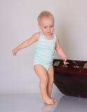 Παιχνίδι κοριτσάκι με τη βαλίτσα στην γκρίζα ανασκόπηση στοκ εικόνες με δικαίωμα ελεύθερης χρήσης