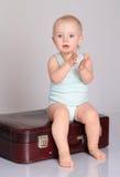 Παιχνίδι κοριτσάκι με τη βαλίτσα στην γκρίζα ανασκόπηση στοκ εικόνα