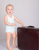 Παιχνίδι κοριτσάκι με τη βαλίτσα στην γκρίζα ανασκόπηση στοκ φωτογραφίες με δικαίωμα ελεύθερης χρήσης