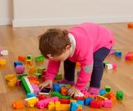 Παιχνίδι κοριτσάκι μικρών παιδιών με το έξυπνο τηλέφωνο μεταξύ των παιχνιδιών Στοκ Εικόνα