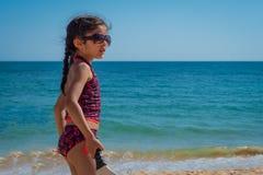 Παιχνίδι κοριτσιών με τη ρακέτα σε μια παραλία στις διακοπές στοκ εικόνες