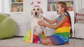 Παιχνίδι κοριτσιών με το σκυλί - που ντύνει ίδια απόθεμα βίντεο