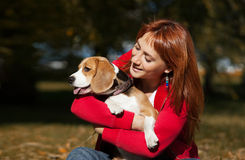 Παιχνίδι κοριτσιών με το σκυλί της στο πάρκο φθινοπώρου στοκ εικόνες