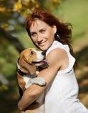 Παιχνίδι κοριτσιών με το σκυλί της στο πάρκο φθινοπώρου στοκ φωτογραφία