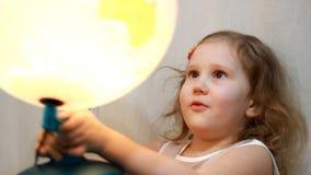 Παιχνίδι κοριτσιών παιδιών με μια φωτισμένη σφαίρα Το μωρό μελετά τη γεωγραφία και έναν χάρτη του κόσμου απόθεμα βίντεο