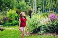 Παιχνίδι κοριτσιών παιδιών με τον ψεκαστήρα κήπων στην καυτή θερινή ημέρα Στοκ εικόνα με δικαίωμα ελεύθερης χρήσης
