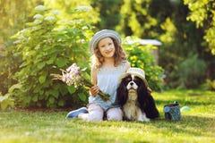 παιχνίδι κοριτσιών παιδιών με το σκυλί σπανιέλ της στο θερινό κήπο Στοκ Εικόνες