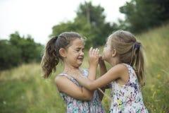 Παιχνίδι κοριτσιών φίλων παιδιών που ψιθυρίζει στη χλόη λουλουδιών στο vac Στοκ εικόνα με δικαίωμα ελεύθερης χρήσης