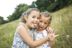 Παιχνίδι κοριτσιών φίλων παιδιών που ψιθυρίζει στη χλόη λουλουδιών στο vac Στοκ Φωτογραφία