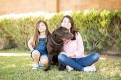 Παιχνίδι κορών μητέρων με το σκυλί στοκ φωτογραφία