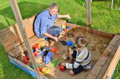 Παιχνίδι μητέρων αγοριών οικογενειακών παιδιών στο σκάμμα το καλοκαίρι Στοκ Εικόνες