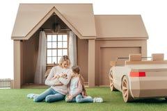 παιχνίδι μητέρων και κορών με το λατρευτό κουτάβι του Λαμπραντόρ καθμένος στη χλόη μπροστά από το σπίτι χαρτονιού στοκ εικόνα