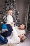 Παιχνίδι μητέρων και πατέρων με το γιο στο υπόβαθρο Χριστουγέννων στοκ εικόνα