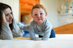Παιχνίδι μητέρων με το μωρό της στην κρεβατοκάμαρα ευτυχής οικογένεια στοκ εικόνα με δικαίωμα ελεύθερης χρήσης