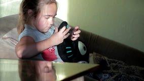 Παιχνίδι μικρών κοριτσιών θερμά με το τηλέφωνο στο σπίτι Εξάρτηση παιδιών ` s στις συσκευές απόθεμα βίντεο