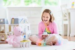 Παιχνίδι μικρών κοριτσιών με το σπίτι κουκλών Παιδί με τα παιχνίδια στοκ εικόνα με δικαίωμα ελεύθερης χρήσης