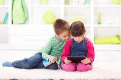 Παιχνίδι μικρών κοριτσιών σε έναν υπολογιστή ταμπλετών Στοκ φωτογραφία με δικαίωμα ελεύθερης χρήσης