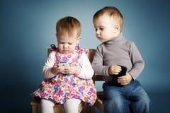 Παιχνίδι μικρών παιδιών και κοριτσιών με τα κινητά τηλέφωνα Στοκ εικόνα με δικαίωμα ελεύθερης χρήσης