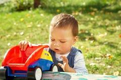 Παιχνίδι μικρών παιδιών με ένα φορτηγό παιχνιδιών στοκ εικόνες