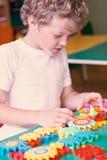 Παιχνίδι μικρών παιδιών με τα ζωηρόχρωμα πλαστικά τούβλα στον πίνακα Μικρό παιδί που έχει τη διασκέδαση και που χτίζει έξω του έξ Στοκ Εικόνες