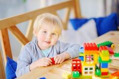 Παιχνίδι μικρών παιδιών με τους ζωηρόχρωμους πλαστικούς φραγμούς στον παιδικό σταθμό ή στο σπίτι Στοκ Εικόνες