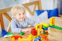 Παιχνίδι μικρών παιδιών με τους ζωηρόχρωμους πλαστικούς φραγμούς στον παιδικό σταθμό ή στο σπίτι Στοκ φωτογραφία με δικαίωμα ελεύθερης χρήσης
