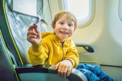 Παιχνίδι μικρών παιδιών με το αεροπλάνο εγγράφου στο εμπορικό αεριωθούμενο αεροπλάνο Στοκ φωτογραφία με δικαίωμα ελεύθερης χρήσης