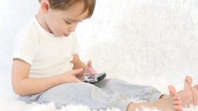 Παιχνίδι μικρών παιδιών με το smartphone στο άσπρο υπόβαθρο Κινηματογράφηση σε πρώτο πλάνο φιλμ μικρού μήκους