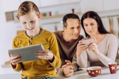 Παιχνίδι μικρών παιδιών στην ταμπλέτα στην κουζίνα Στοκ φωτογραφία με δικαίωμα ελεύθερης χρήσης