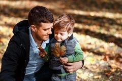 Παιχνίδι μπαμπάδων και γιων έξω το φθινόπωρο στο πάρκο στοκ εικόνες με δικαίωμα ελεύθερης χρήσης